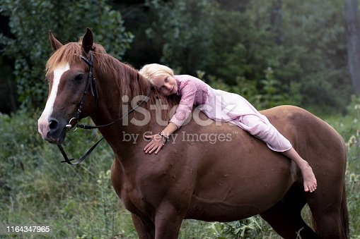 innocent blonde girl with horse in the forest. beautiful Caucasian girl with long blonde hair in a pink dress lies on a brown horse and hugs her. barefoot child on horseback. innocent childhood