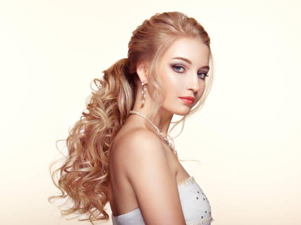 blonde mädchen mit langen und glänzenden lockiges haar - brautstyling stock-fotos und bilder