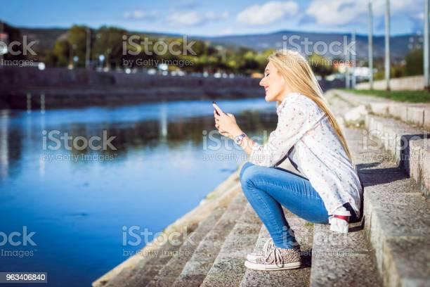 Blondynka Z Telefonem Nad Rzeką - zdjęcia stockowe i więcej obrazów 20-29 lat