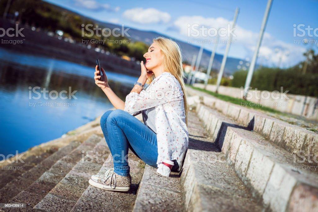 Blond tjej med telefon vid floden - Royaltyfri 20-29 år Bildbanksbilder