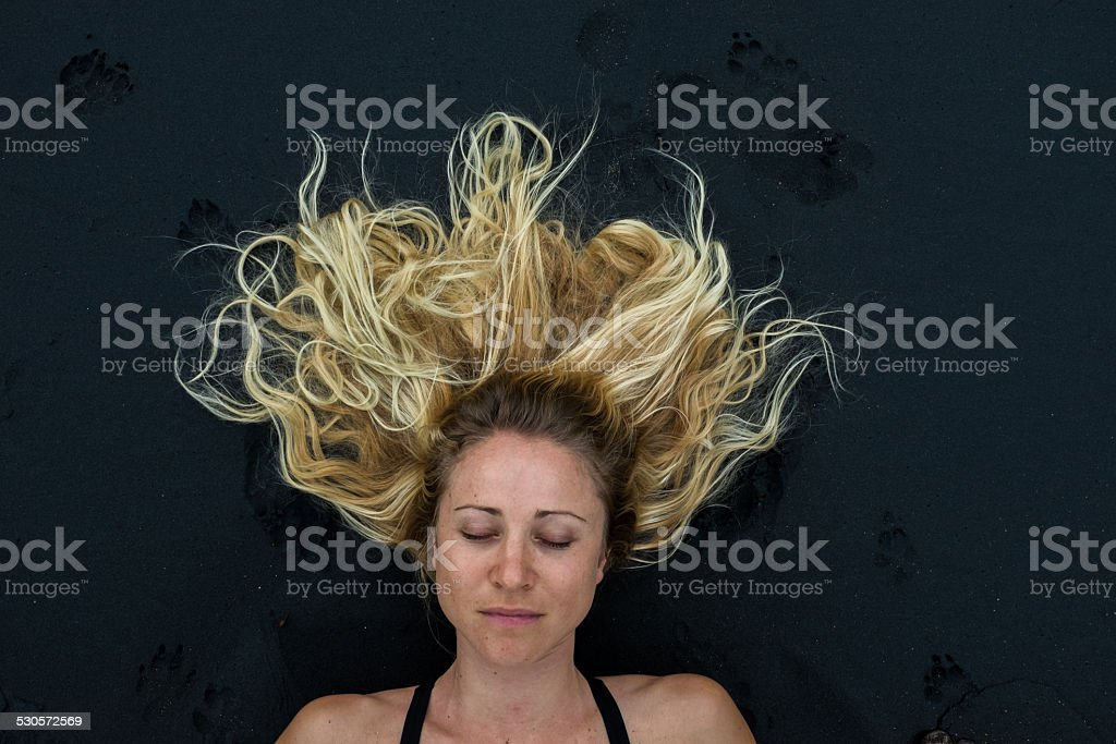 Blonde girl with thick hair lying on black sand stock photo