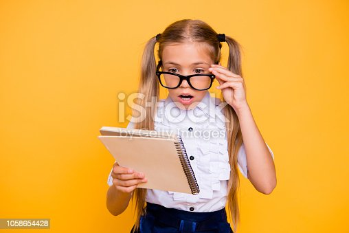 531869550 istock photo Blonde hair confused facial expression concept. Close up photo portrait of puzzled thoughtful with open mouth little schoolchild adjusting glasses staring at text in copybook isolated background 1058654428