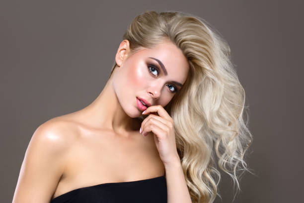 blonde haar vrouw portret met blauwe ogen en gezonde lange glanzende golvende kapsel. volume shampoo. blonde krullend gepermanent haar en heldere make-up.  schoonheidssalon en haircare concept. - verleiding stockfoto's en -beelden