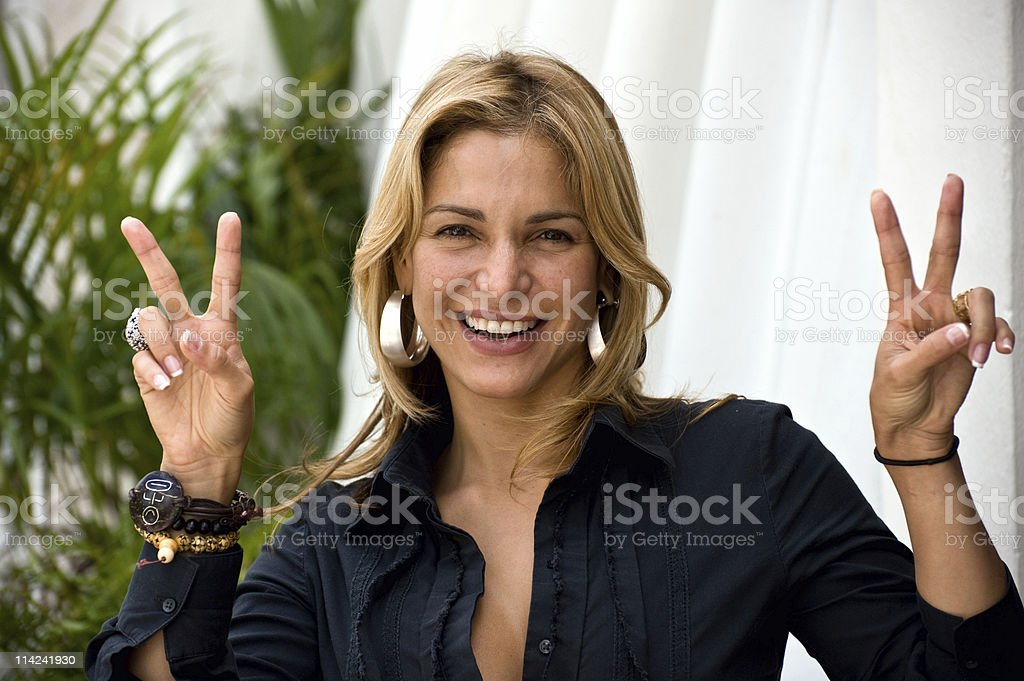 Blonde Hispanic Woman Making Peace Sign with Both Hands royalty-free stock photo