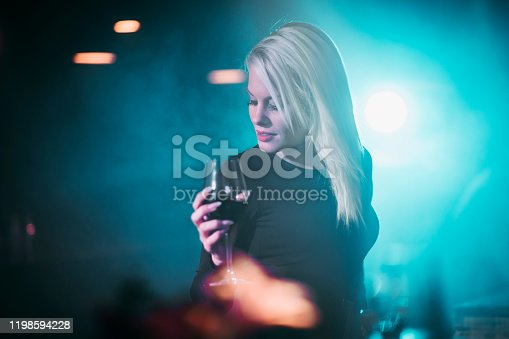 A young blond female enjoying the night in a club with a wine glass in her hand.