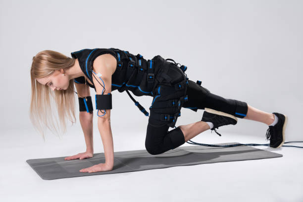 Blonde in an electric muscular suit for stimulation makes an exercise on the rug. stock photo