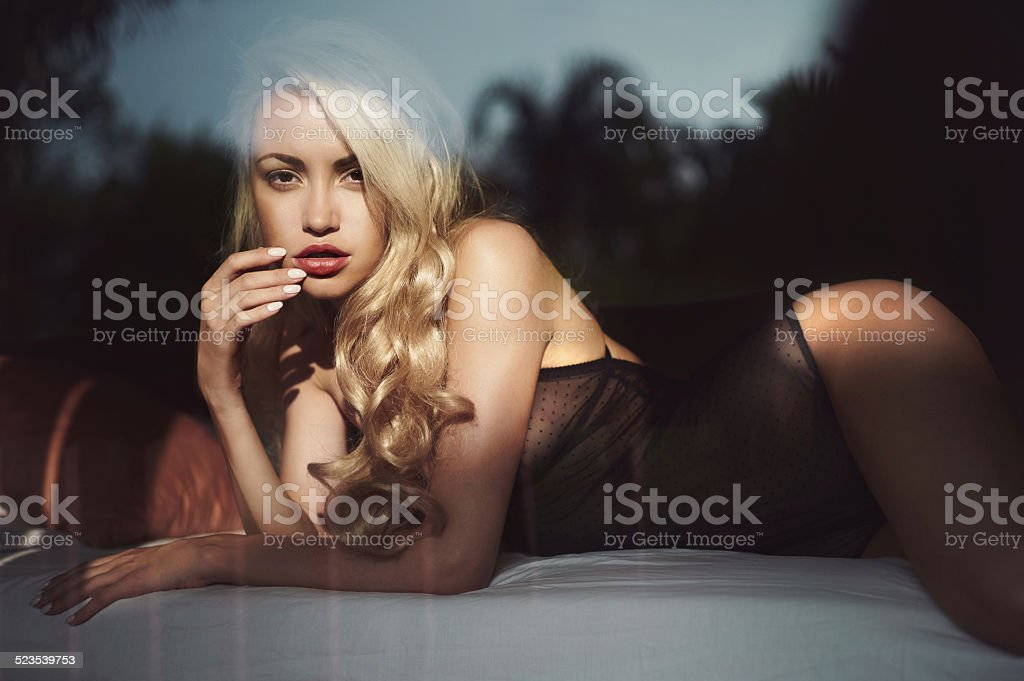 Blonde in bed in the sun stock photo