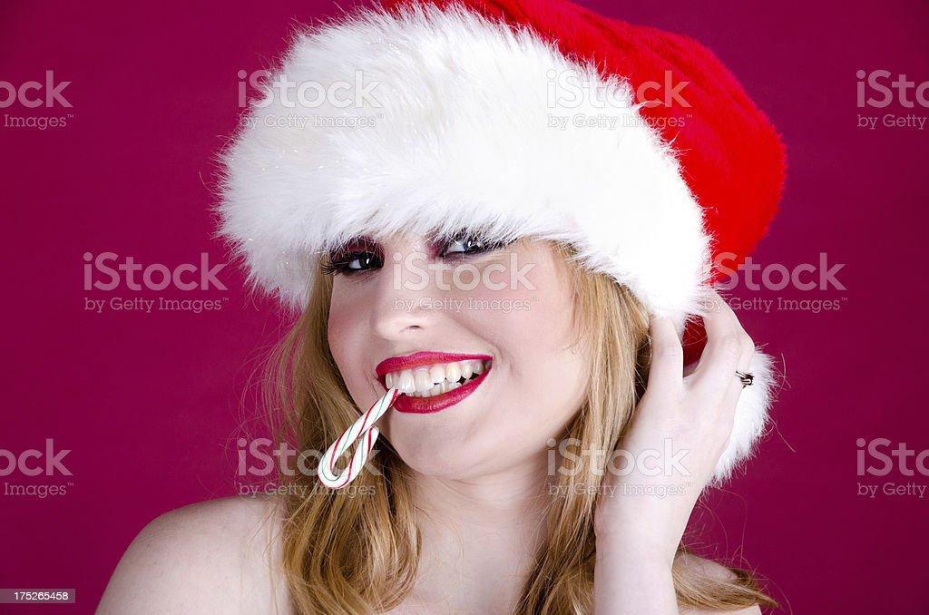 Blonde in Santa hat with big grin and candy cane. royalty-free stock photo