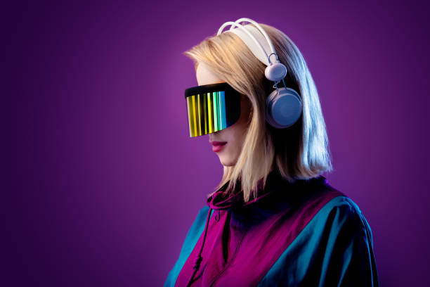 Blonde in VR glasses and headphones on pink background stock photo
