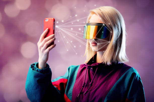 Blonde in VR glasses hold mobile phone with face scanning algorithm stock photo
