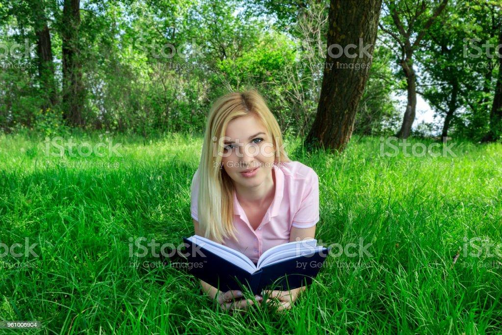 Blondine liest ein Buch in einem Park auf dem Rasen - Lizenzfrei Akademisches Lernen Stock-Foto