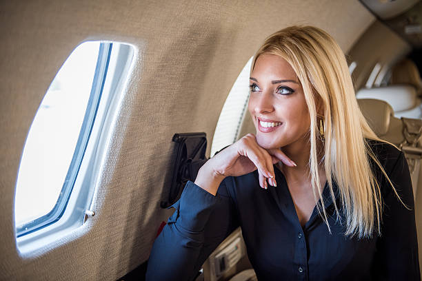 Blonde lady looking through the aeroplane window stock photo