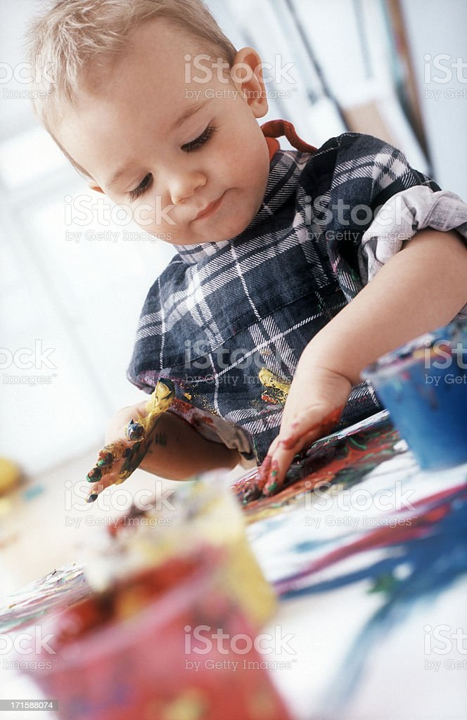 Blonde little boy is busy painting with his fingers royalty-free stock photo