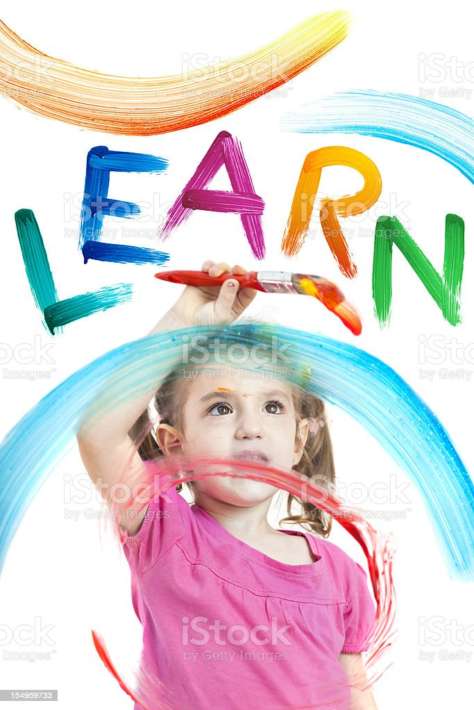 Blonde little girl painting the word learn on window royalty-free stock photo