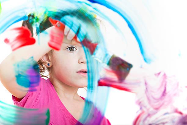 blonde kleine mädchen malen mit farben auf fenster - glasmalerei stock-fotos und bilder