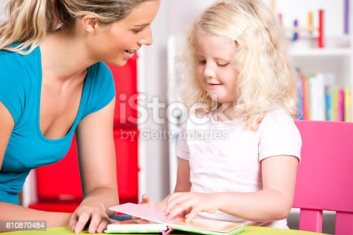 istock Blonde Little Girl Reading With Her Carer At Nursery 610870484