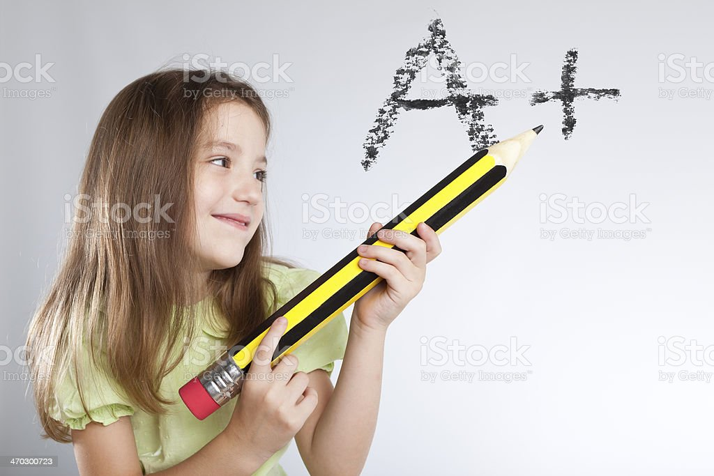 Blonde little girl writing with giant pencil royalty-free stock photo