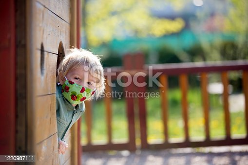 Blonde little toddler child wearing protective mask, playing on the playground, spring sunny day