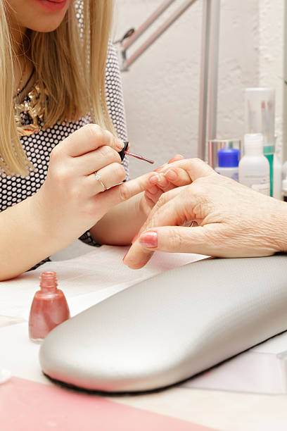 Blonde manicurist polishing fingernails stock photo