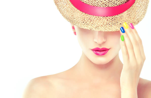 blonde model in a straw hat with bright pink makeup and earrings-beads. - nailstudio stock-fotos und bilder