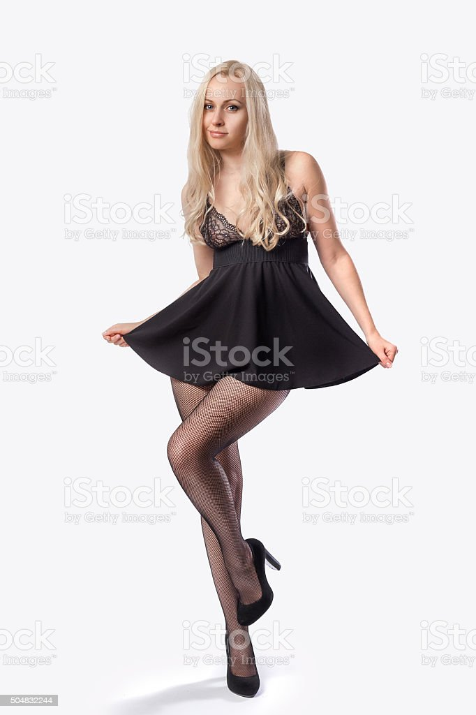 Blonde model in sexy short black dress and pantyhose stock photo