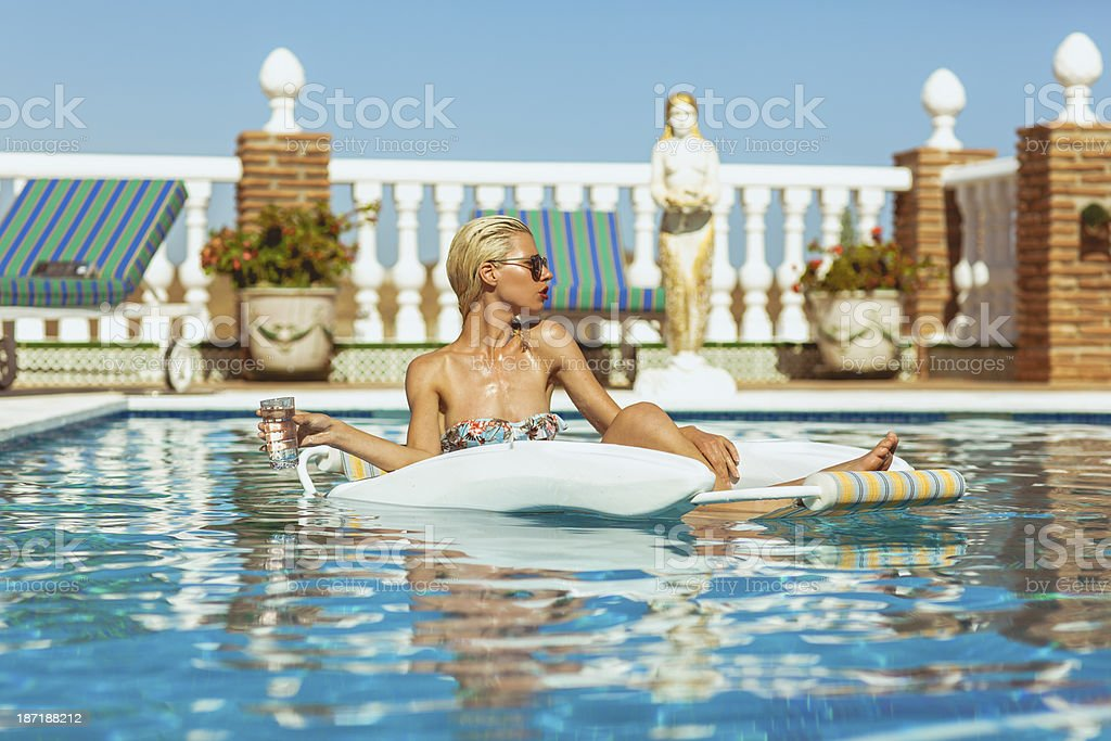 Blonde model relaxing in pool royalty-free stock photo