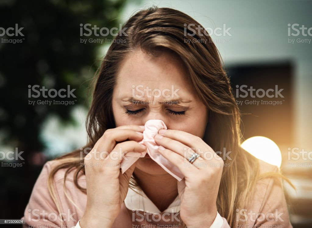 Blonde office worker working late sneezes into a tissue stock photo