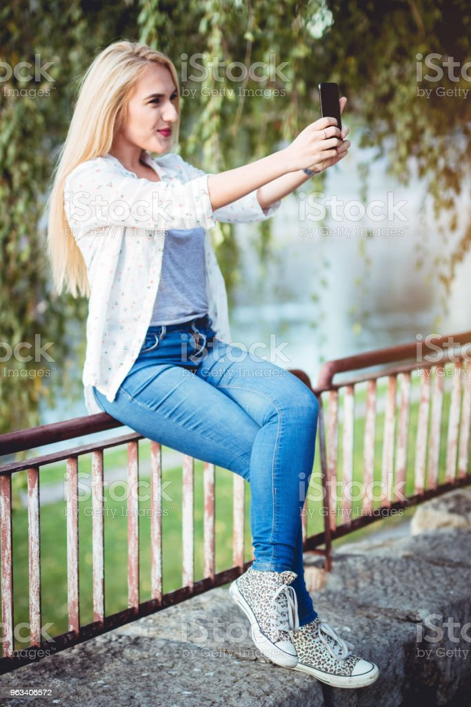 Blonde on railing taking a selfie - Zbiór zdjęć royalty-free (20-29 lat)