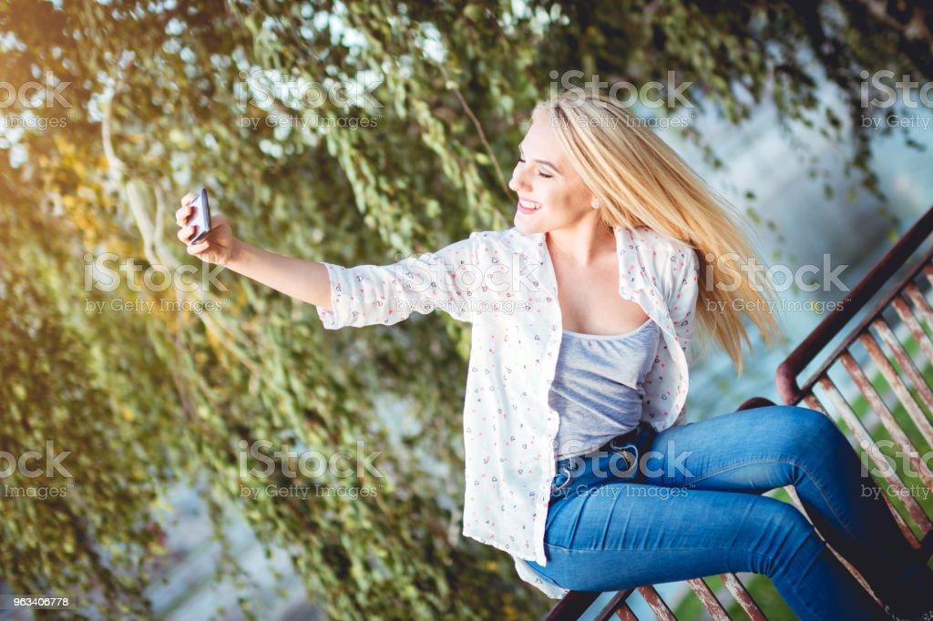 Blondin på räcke att ta en selfie - Royaltyfri 20-29 år Bildbanksbilder