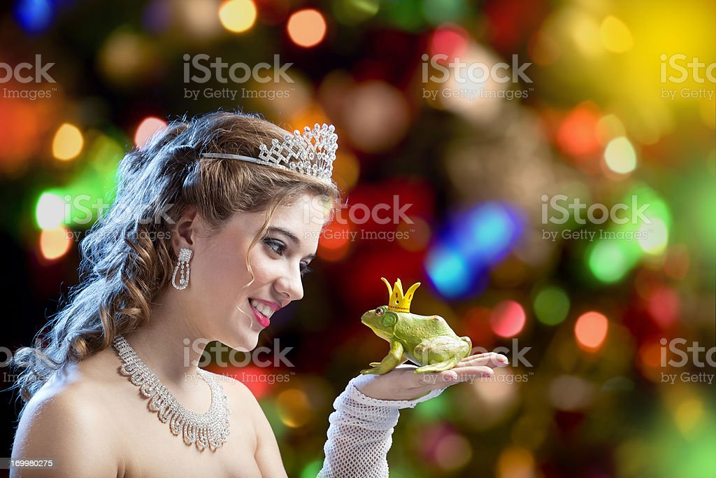 Blonde princess about to kiss a frog stock photo
