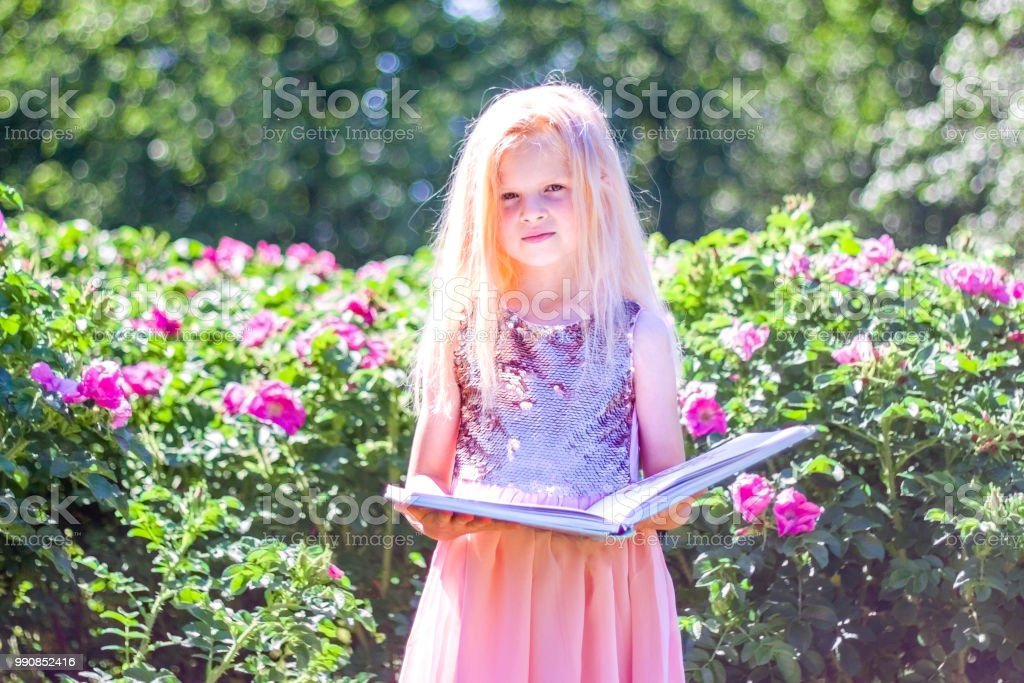 Blonde Prodigy Little Girl Is Reading Magic Book In Garden