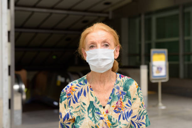 Blonde senior woman wearing mask for protection from corona virus outbreak at subway train station outdoors stock photo