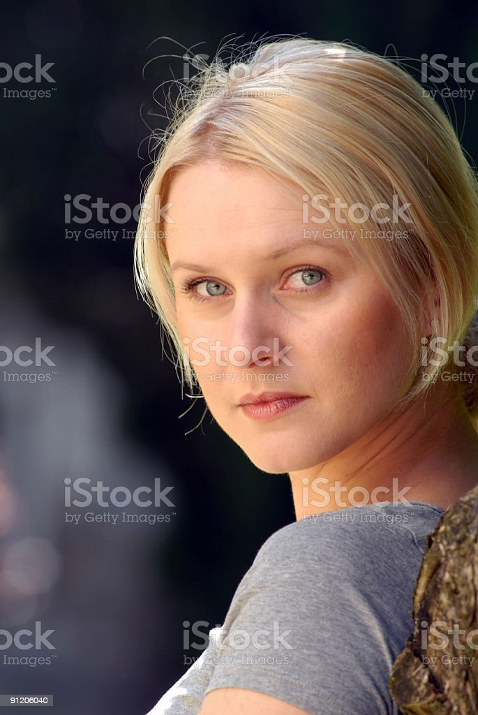 Blonde serious face looking over shoulder royalty-free stock photo