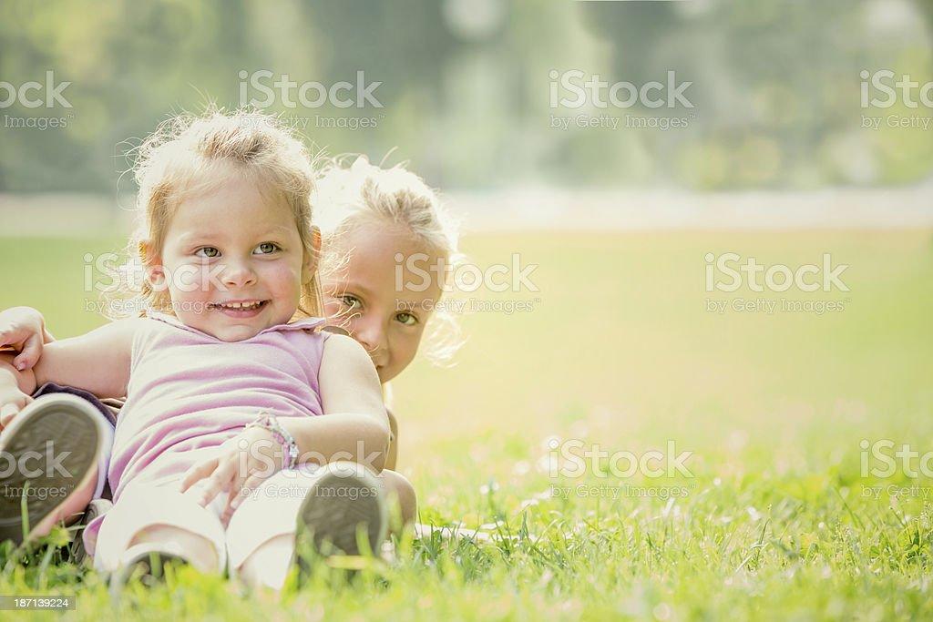 Blonde sisters having fun at park stock photo