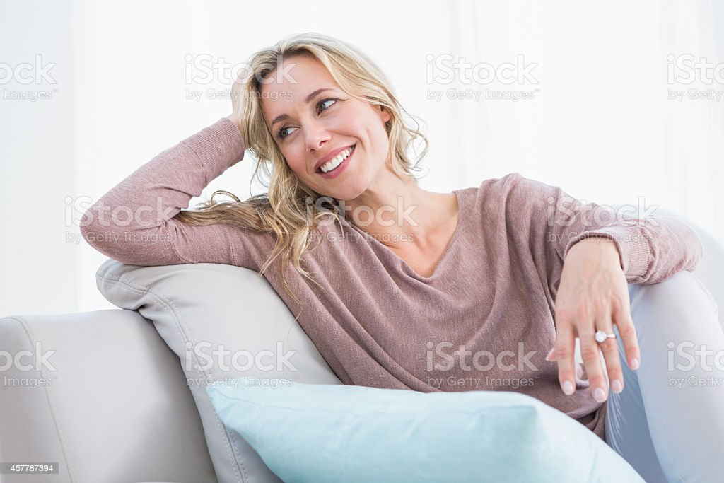 Blonde sitting on couch smiling and thinking stock photo