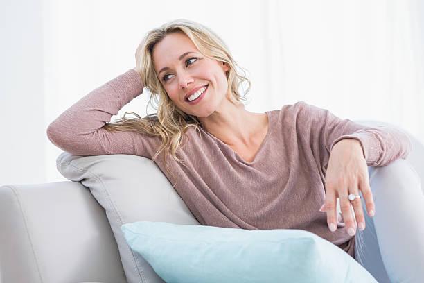 Blonde sitzt auf Sofa lächelnd und denken – Foto