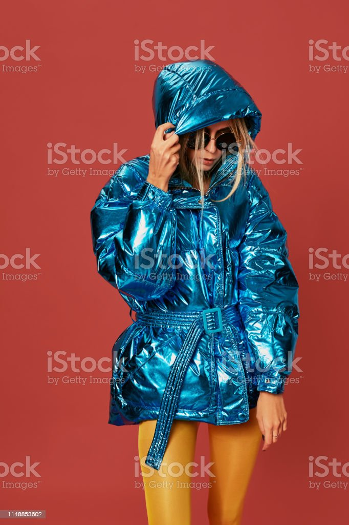 Close up fashion photo of young woman covering herself with hood. She...
