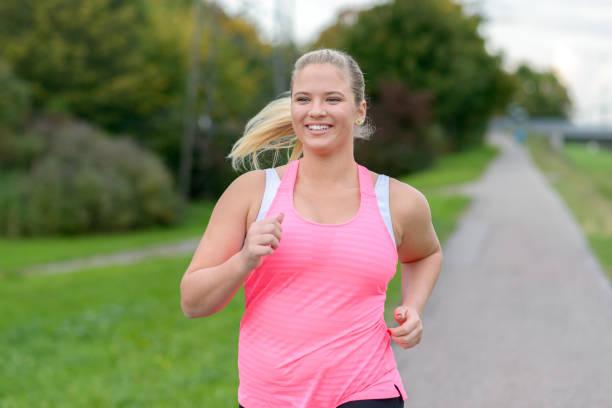 blonde lächelnde frau entlang läuft - laufveranstaltungen stock-fotos und bilder
