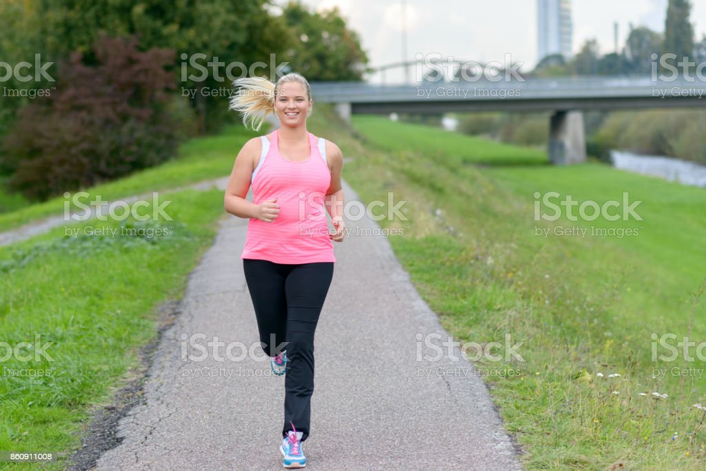 Blonde smiling woman running along river stock photo