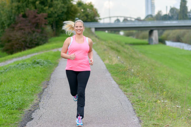 blonde smiling woman running along river - fat nutrient stock photos and pictures