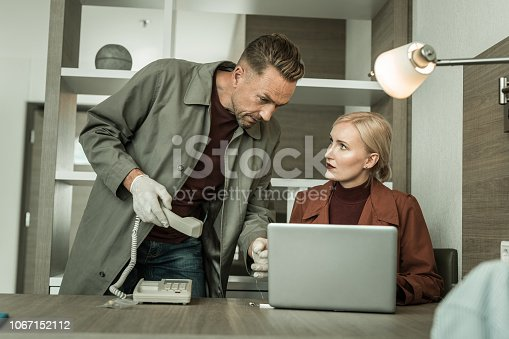 istock Blonde spy wearing all red outfit installing virus program on the laptop 1067152112
