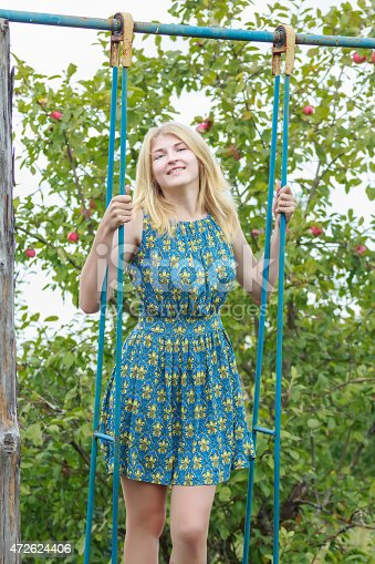 Blonde student girl in feminine silk sundress is standing on handmade swing. Positive young girl is standing in full length on rustic tall blue swing made of metal and wood. Blonde girl is with wheat color shoulder-length hair. Action shot of girl is riding on handmade swing in summer fruit apple garden. Fruit tree green foliage and red ripening apples are at the background. Girl is wearing silk sundress with feminine silhouette of turquoise blue color.