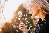 Blonde teenage girl with dandelion in the afternoon sun