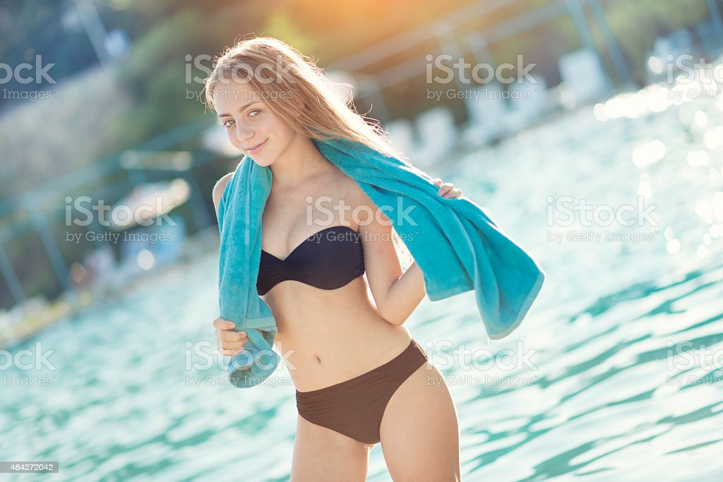 Blonde Teenage Girl with Towel by the Swimming Pool stock photo