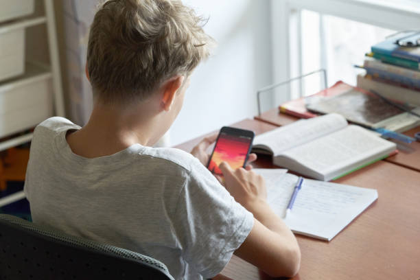 Blonde teenager boy doing school homework sitting at the table with a pen in a hand. A Caucasian blonde teenager boy sitting at a table and looking at smartphone. Blonde teenager boy doing school homework but  distracted by a smartphone. bad posture stock pictures, royalty-free photos & images