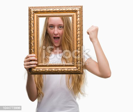 808681534 istock photo Blonde teenager woman holding vintage frame art annoyed and frustrated shouting with anger, crazy and yelling with raised hand, anger concept 1044773996