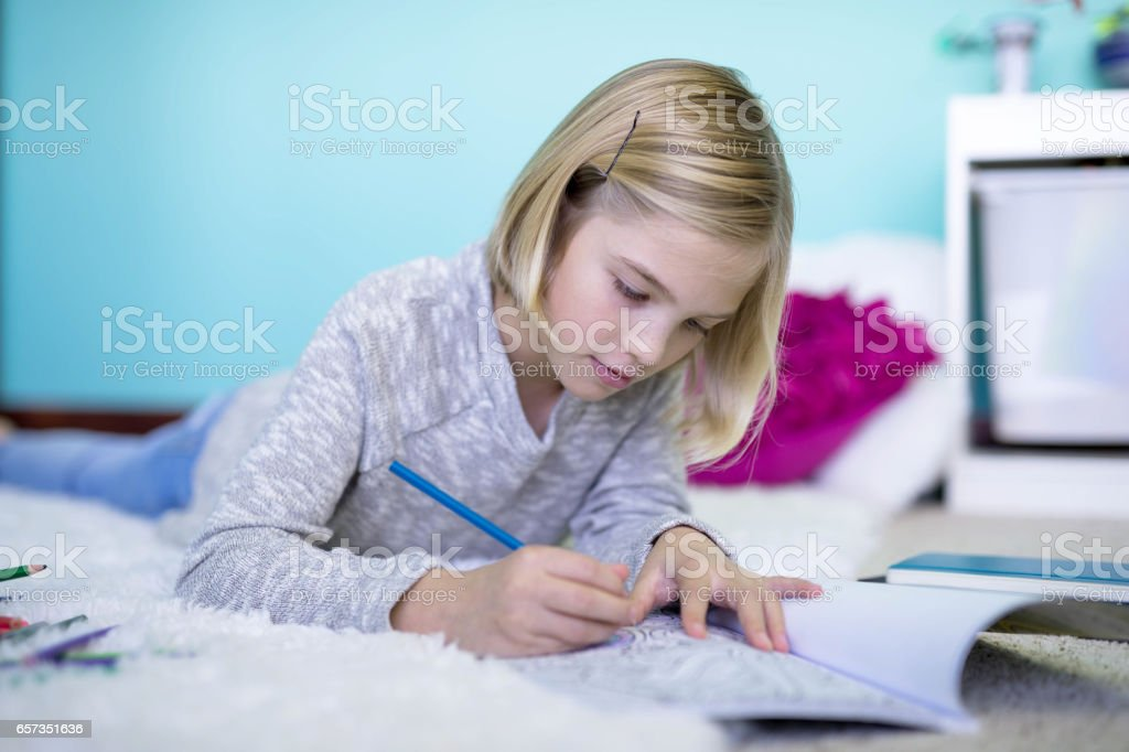 Blonde ten-year old girl studying on floor stock photo