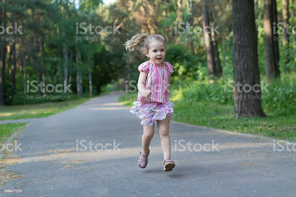 Blonde three years old girl running on asphalt park footpath stock photo