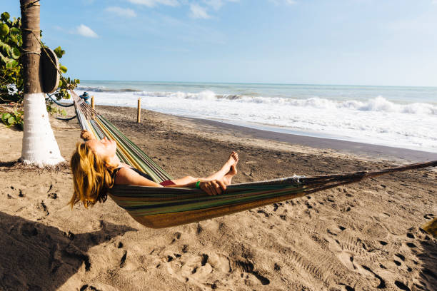 A blonde tourist enjoys the sun and sea in a hammock on the Caribbean coast of Colombia A blonde tourist enjoys the sun and sea in a hammock on the Caribbean coast of Colombia palomino stock pictures, royalty-free photos & images