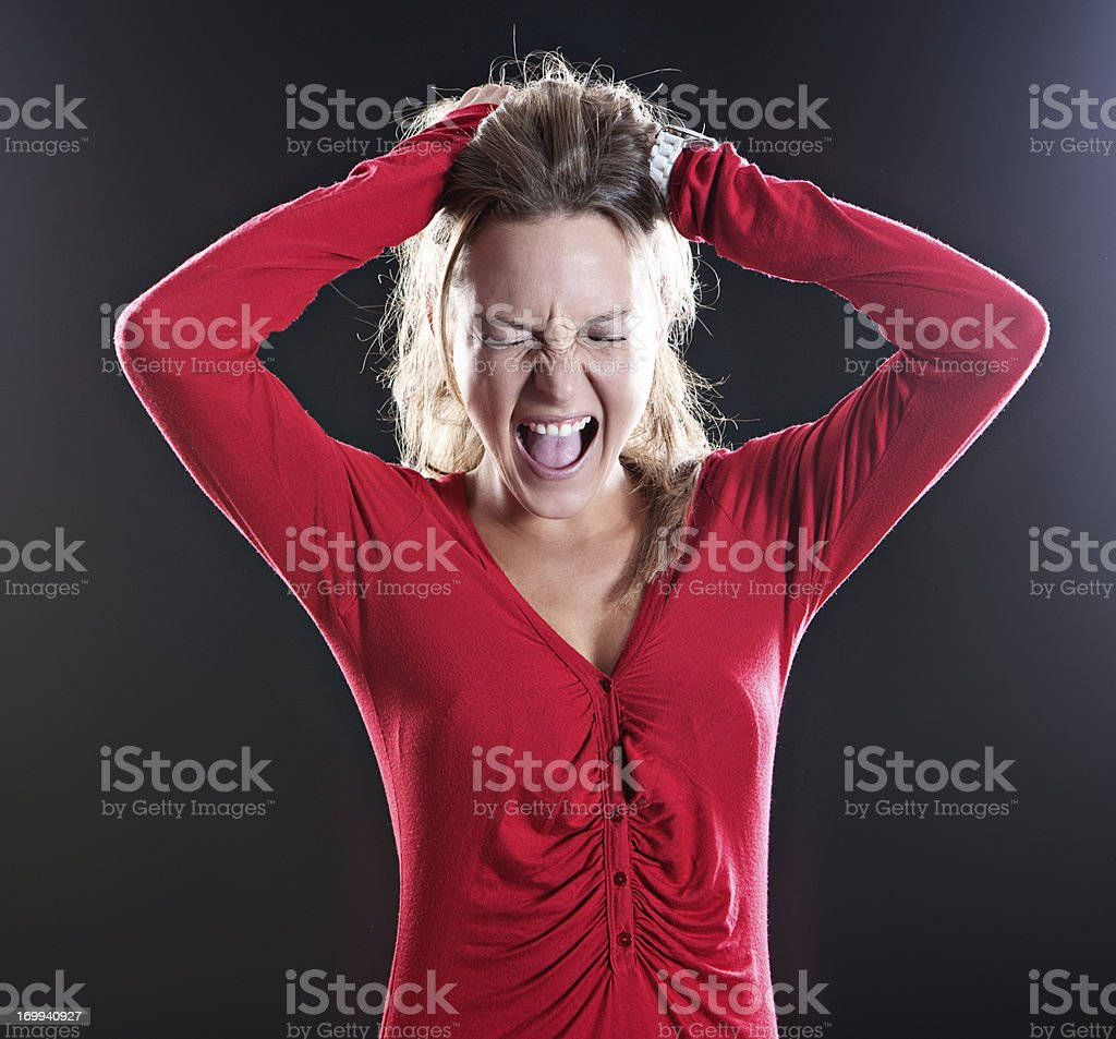 Blonde wearing red  holds head and yells, eyes squeezed shut stock photo